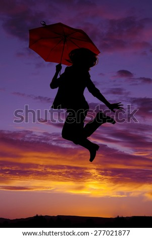 A silhouette of a woman jumping up in her rain boots, and holding an umbrella.