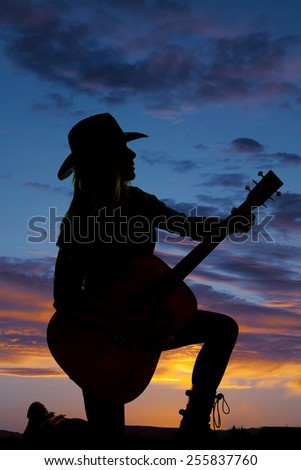 A silhouette of a woman kneeling on the ground in the outdoors holding on to her guitar. - stock photo