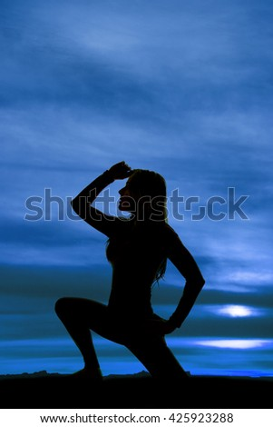 A silhouette of a woman kneeling with  her hand up by her head. - stock photo