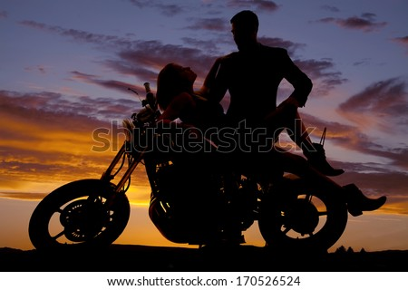 A silhouette of a woman laying back on the motorbike with her man looking down at her. - stock photo