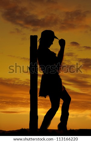 A silhouette of a woman leaning back against a post touching the brim of her hat. - stock photo