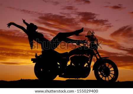 A silhouette of a woman leaning back on her bike with her arms up and feet up. - stock photo
