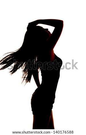 A silhouette of a woman leaning back with the wind blowing her hair. - stock photo