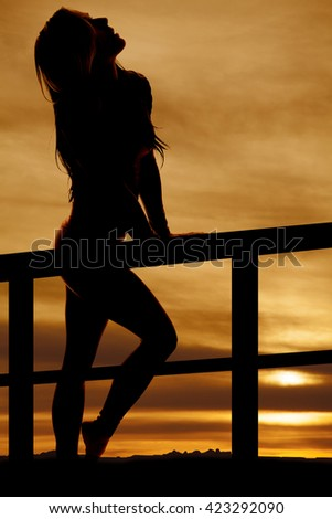 A silhouette of a woman leaning by a fence, looking up into the sky. - stock photo