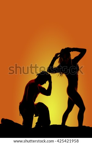 a silhouette of a woman looking back while her cowboy is kneeling to pray. - stock photo