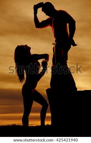 a silhouette of a woman looking up at a cowboy who is standing up on a rock - stock photo