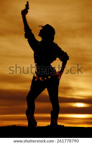 a silhouette of a woman looking up holding on to her pistol. - stock photo