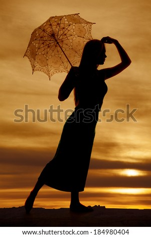 A silhouette of a woman looking while holding on to her umbrella. - stock photo