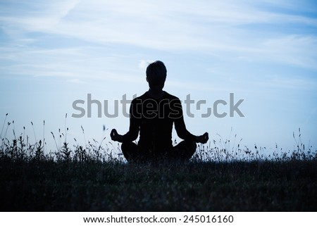A silhouette of a woman meditating ,intentionally toned image.Meditation - stock photo