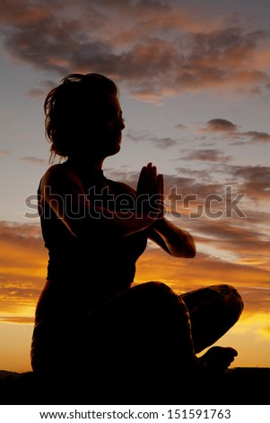 a silhouette of a woman meditating sitting down.