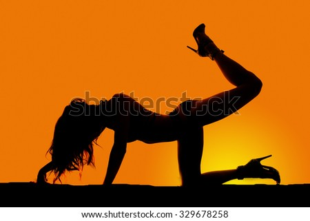 A silhouette of a woman on her knee with her leg kicked up.