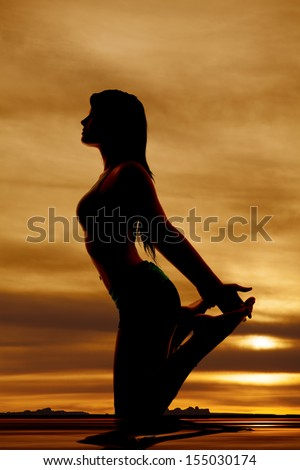 A silhouette of a woman  on her knees holding up her feet. - stock photo