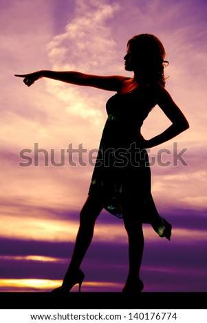a silhouette of a woman pointing with a serious expression on her face. - stock photo