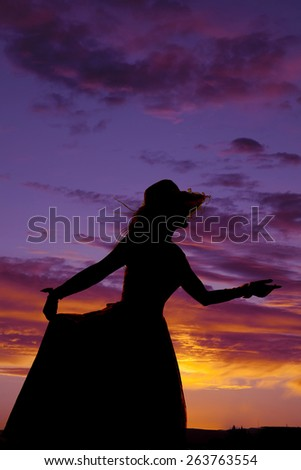 A silhouette of a woman reaching out in her formal dress with a hat. - stock photo