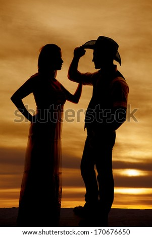 A silhouette of a woman reaching up to touch her cowboys arm.