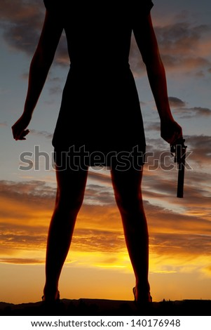 a silhouette of a woman's legs and she is holding a gun in her hand - stock photo