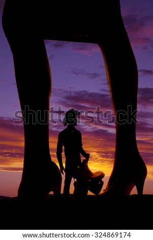 A silhouette of a woman's legs in heels with a cowboy in between them. - stock photo