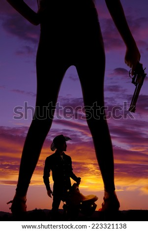 A silhouette of a woman's legs with a cowboy holding on to a saddle in between them. - stock photo