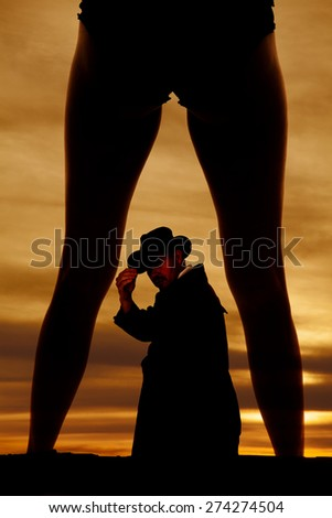 a silhouette of a woman's legs with a cowboy in between her legs. - stock photo