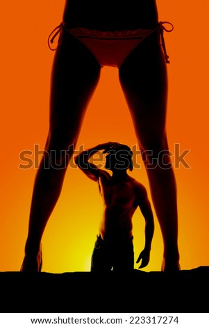 A silhouette of a woman's legs with a cowboy in the middle of them. - stock photo
