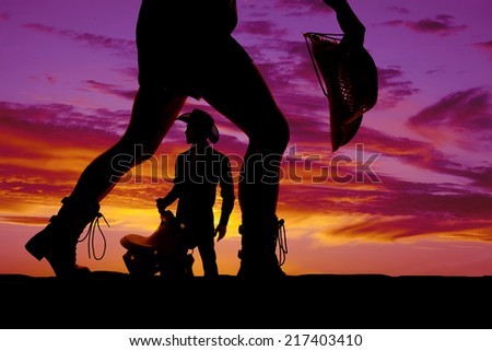 A silhouette of a woman's legs with a cowboy silhouette in the middle of them. - stock photo
