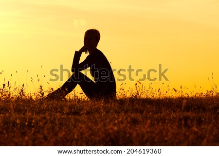 A silhouette of a woman sitting and enjoy in the nature. - stock photo