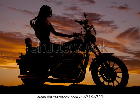 A silhouette of a woman sitting on a motorcycle. - stock photo