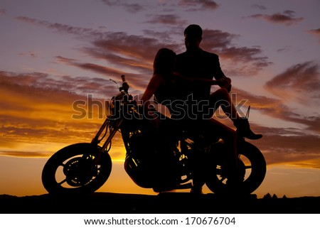 A silhouette of a woman sitting on a motorcycle her man is looking down at her. - stock photo
