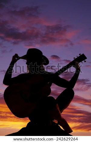 a silhouette of a woman sitting on a rock touching the brim of her hat, holding onto her guitar. - stock photo