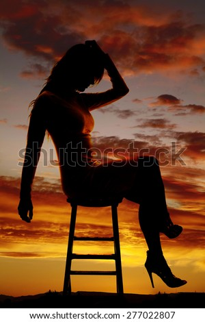 A silhouette of a woman sitting on a stool, with her head down in sadness.