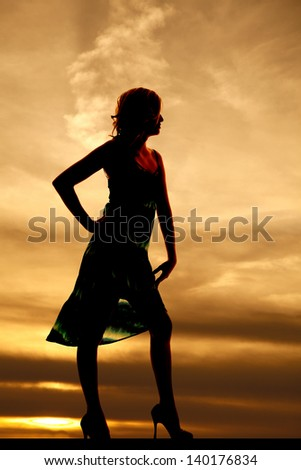 a silhouette of a woman standing in front of a beautiful sky - stock photo