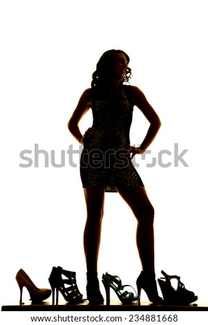 A silhouette of a woman standing in her dress and heels with shoes all around her. - stock photo