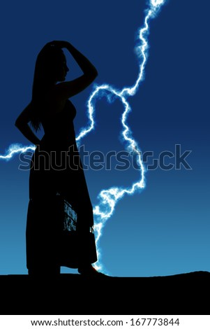 A silhouette of a woman standing in the outdoors with a dress on. - stock photo