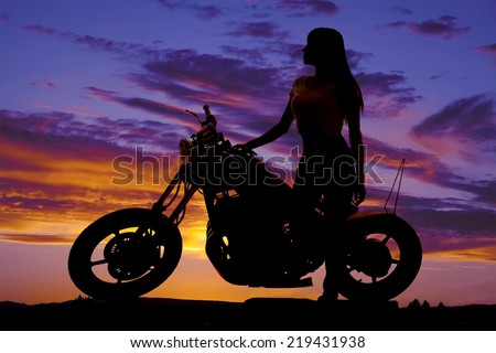 A silhouette of a woman standing next to a motorcycle looking to the side. - stock photo
