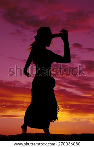 A silhouette of a woman touching the brim of her hat in the outdoors. - stock photo