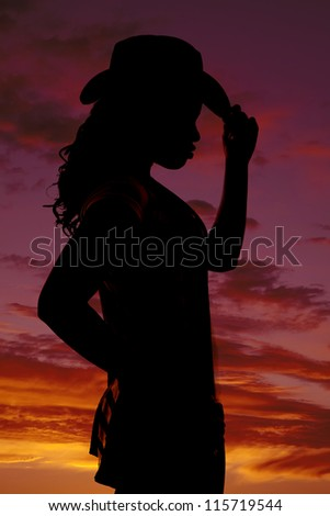 a silhouette of a woman touching the brim of her hat with a beautiful  colorful sky behind her. - stock photo