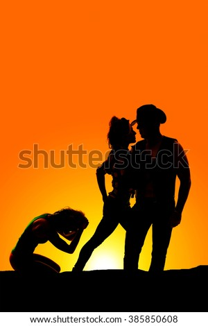 A silhouette of a woman upset while her cowboy holds another woman. - stock photo