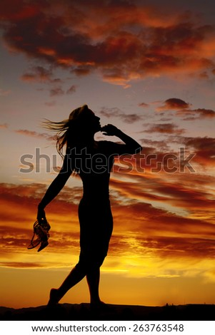 A silhouette of a woman walking along a path, holding on to her shoes. - stock photo