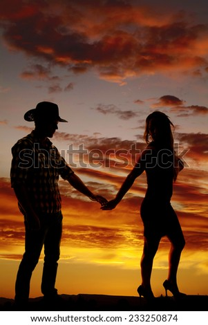A silhouette of a woman walking away from her cowboy. - stock photo