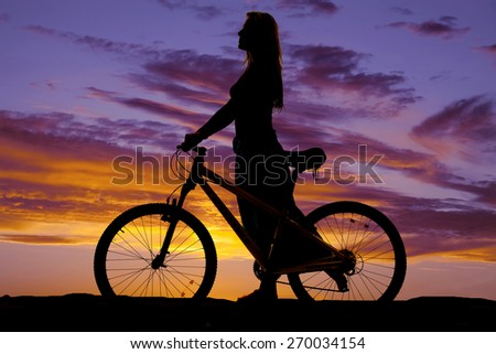 A silhouette of a woman walking with her bike. - stock photo