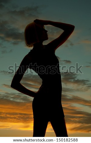A silhouette of a woman with her hand on her head in a short dress. - stock photo