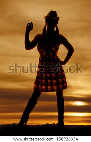 A silhouette of a woman with her hand up in the outdoors. - stock photo
