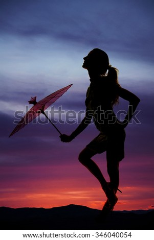A silhouette of a woman with her umbrella in the outdoors.
