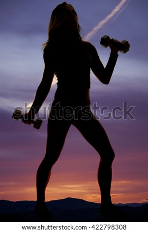 A silhouette of a woman working out her arms in the out doors.