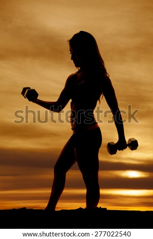 A silhouette of a woman working out with her weights. - stock photo