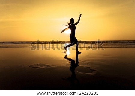A silhouette of a women running at sunset on beach