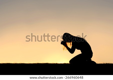 A silhouette of a young Christian woman is bowing her head in prayer, and desperation outside during sunset. - stock photo