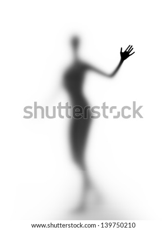 A silhouette of a young woman seen through frosted glass - stock photo