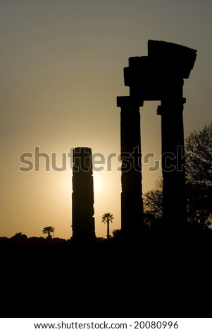 A silhouette of an ancient Greek temple against setting sun