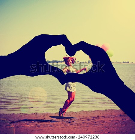 a silhouette of hands in the shape of a heart over a background toned with a retro vintage instagram filter effect - stock photo